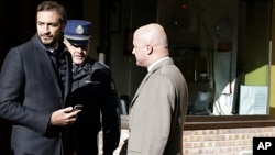 Italian journalists Gianluigi Nuzzi (R), and Emiliano Fittipaldi (L) talk with a Vatican Gendarmie guard at the Vatican City's Perugino entrance Nov. 24, 2015.