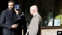 Italian journalists Gianluigi Nuzzi (R), and Emiliano Fittipaldi (L) talk with a Vatican Gendarmie guard at the Vatican City's Perugino entrance Nov. 24, 2015.