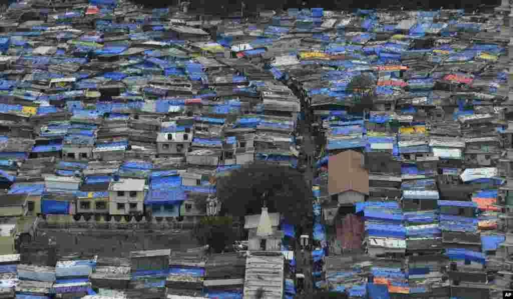 ដំបូលខ្ទមត្រូវបានគ្របដោយក្រណាត់ពណ៌ខៀវដើម្បីការពារពីភ្លៀងនៅទីក្រុង Mumbai ប្រទេសឥណ្ឌា។