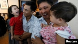 Reuters reporters Wa Lone and Kyaw Soe Oo celebrate with their children after being freed from prison, after receiving a presidential pardon in Yangon, Myanmar, May 7, 2019.