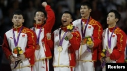 Feng Zhe (L-R) of China and teammates Guo Weiyang, Chen Yibing, Zhang Chenglong and Zou Kai celebrate with their gold medals after taking first place in the men's gymnastics team final in the North Greenwich Arena at the London 2012 Olympic Games, July 30