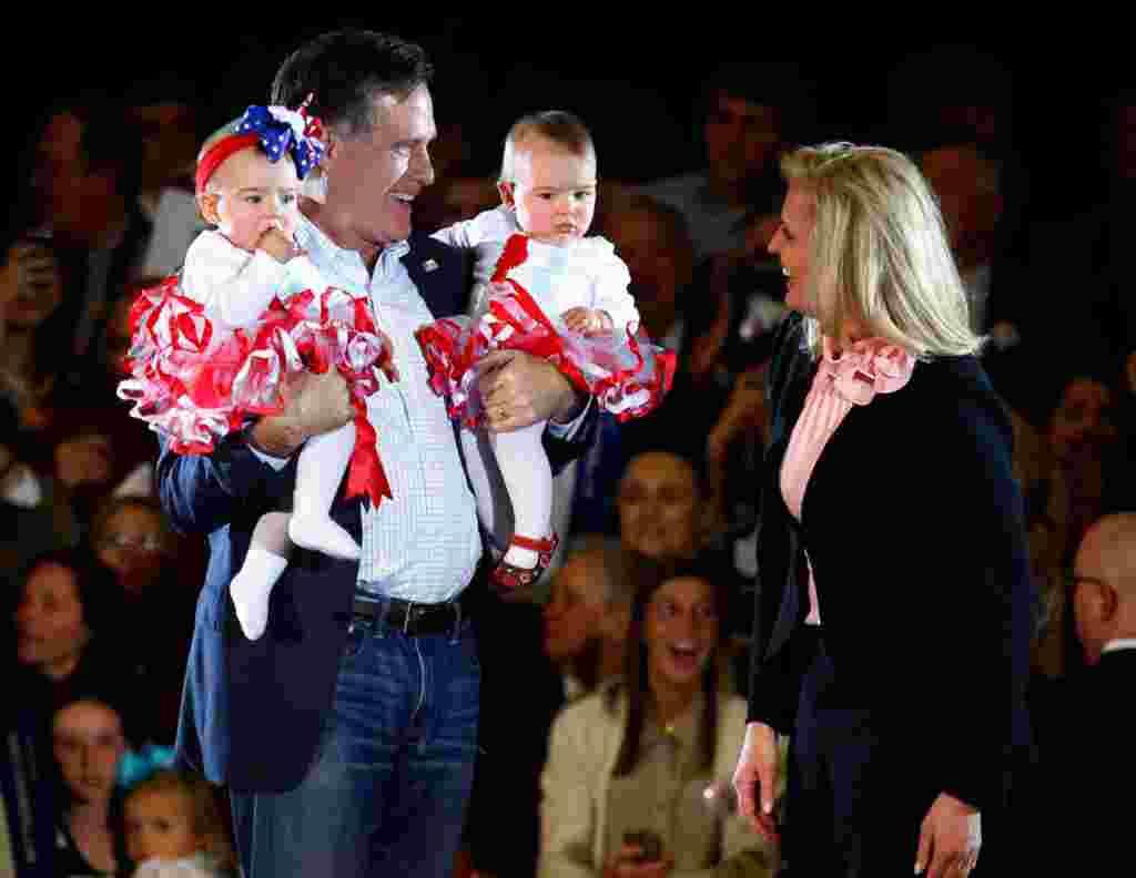 Mitt Romney dan istrinya Ann menggendong bayi-bayi yang dipilih dari kerumunan pendukungnya di Knoxville, Tennessee, 5 Maret 2012 (Reuters).