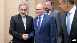 Russian President Vladimir Putin, center, shakes hands with Ali Akbar Velayati, a senior adviser to Iran's Supreme Leader Ayatollah Ali Khamenei, as Russian Foreign Minister Sergey Lavrov, stands at right, at Novo-Ograyovo outside in Moscow, Russia, July 12, 2018.