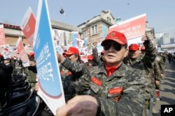 South Korean war veterans hold up their placards during a rally denouncing North Korea's recent threats in Seoul, South Korea, March 25, 2016.