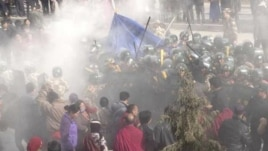 In this handout photo released by The International Campaign for Tibet (ICT) on December 7, 2012, paramilitary policemen are seen closing in on Dorje Rinchen's body after his self-immolation, in Xiahe,  Gansu province, October 23, 2012.