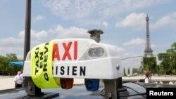تاکسیهای پاريس با نصب روبان زرد، در تجمع اعتراضی عليه فعاليت شرکت مسافربری «اوبر» شرکت میکنند