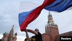 Một cổ động viên Nga vẫy quốc kỳ tại Quảng trường Đỏ.