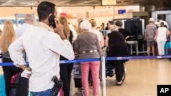 An armed security worker talks on his phone in front of the luggage screening section at the airport of Sharm el-Sheikh, Egypt, Nov. 7, 2015.