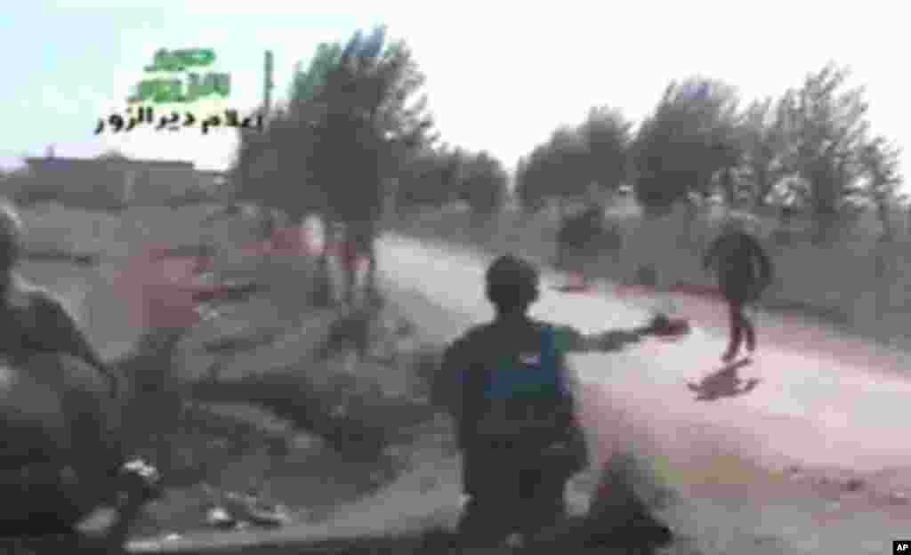 A still from amateur video provided by Ugarit News, shows Syrian rebels during a raid on Hatla, Syria, June 12, 2013.