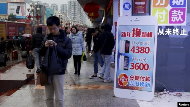 A man checks his smartphone outside a store promoting the Apple iPhone products in the southern Chinese city of Shenzhen, Jan. 26, 2016.