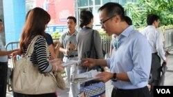 香港立法會選舉會計界參選人梁繼昌(右)在街上向市民派發傳單