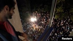 An employee looks at people gathering outside the Greek state television headquarters in Athens, June 11, 2013.