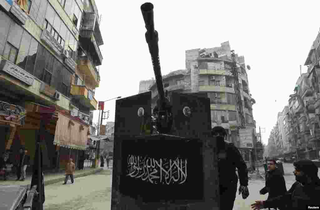 "Anggota Tentara Pembebasan Suriah berdiri di belakang senjata mesin dengan spanduk bertuliskan ""Tiada Tuhan Selain Allah dan Muhammad adalah Rasul Allah"" di distrik Bustan Al Qasr, Aleppo, Suriah (2/1)."