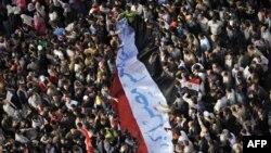 Người biểu tình ở Quảng trường Tahrir cầm cờ Ai Cập với hàng chữ 'Ai Cập vĩ đại hơn quí vị', kêu gọi hội đồng quân nhân cầm quyền từ chức