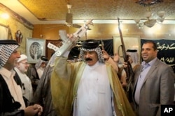 FILE - Iraqi Shiite tribal leaders chant slogans against the al-Qaida-inspired Islamic State of Iraq and the Levant in Baghdad, Iraq, June. 13, 2014.