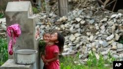 30일 지진 피해를 입은 네팔 발루아 마을에서 한 소녀가 아기를 안은 채 식수대의 물을 마시고 있다.
