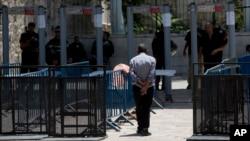 耶路撒冷老城区的阿克萨清真寺前,一名巴勒斯坦男子走向金属探测器。
