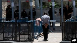 Seorang warga Palestina berjalan melewati detektor logam di komplek masjid Al Aqsa di Yerusalem (19/7).