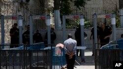 Seorang pria Palestina berjalan melewati alat pendeteksi metal di kompleks Masjid Al Aqsa di kota tua Yerusalem, 19 Juli 2017.