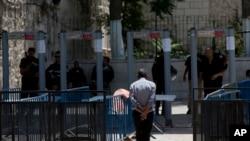 Seorang pria Palestina berjalan menuju sebuah detektor logam di kompleks Masjid Al Aqsa di Kota Tua Yerusalem, 19 Juli 2017. Sebuah perselisihan mengenai detektor logam telah meningkat menjadi pertikaian baru antara Israel dan dunia Muslim.