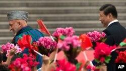 حامد کرزی، رئیس جمهور افغانستان با شی جنگپنگ، همتای چینایی خود در جریان یک سفر رسمی در بیجنگ در ماه سپتمبر سال ۲۰۱۳.
