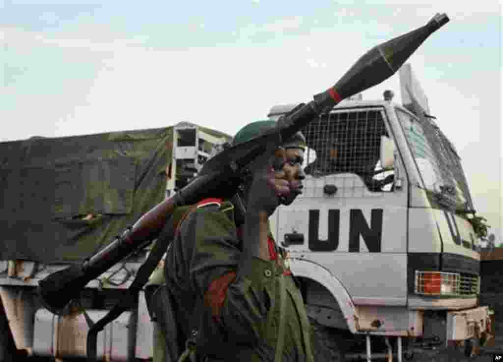 FILE - In this Nov. 23, 2008 file photo, a Congolese government soldier (FARDC) stands guard by a UN truck at the Kibati checkpoint north of Goma, eastern Congo. U.N. peacekeepers deployed to Congo more than a decade ago after civil war drew in troops fro