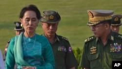 미얀마의 실권자인 아웅산 수치 외무장관(왼쪽)이 군 최고사령관 민 아웅 흘라잉(오른쪽) 등 미얀마 군부 인사들과 대화하고 있다. (자료사진)