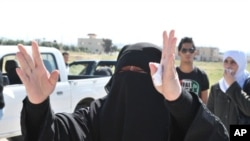 A Syrian woman, who has relatives in the Syrian city of Deraa, gestures at the Jordanian side of the border with Syria that has been closed, April 25, 2011