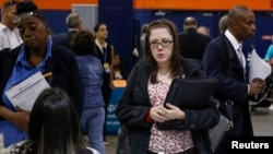 FILE - People speak with recruiters at a job fair in Uniondale, New York, Oct. 7, 2014.