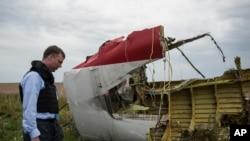 Một nhân viên của Tổ chức An ninh và Hợp tác châu Âu xem xét các mảnh vỡ của chiếc máy bay xấu số.