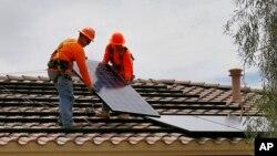 美国工人正在亚利桑那州一家住房的屋顶上安装太阳能板。(2016年6月1日)