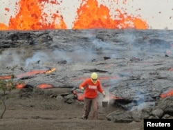 A geologist is collecting sample of molten lava from 2011 Kamoamoa eruption, at Kilauea Volcano, Hawaii, U.S., March 6, 2011.