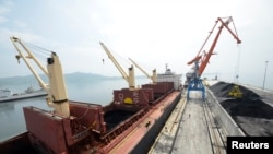 A cargo ship is loaded with coal during the opening ceremony of a new dock at the North Korean port of Rajin in 2014. United Nations Security Council sanctions target North Korea's coal exports.
