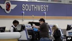 美国西南航空公司的工作人员在为乘客办理登机手续