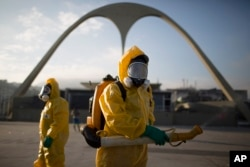 FILE - Health workers stand in the Sambadrome spraying insecticide to combat the Aedes aegypti mosquito that transmits the Zika virus in Rio de Janeiro, Brazil, Jan. 26, 2016.