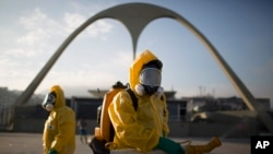 FILE - In this Tuesday, Jan. 26, 2016, photo, a health workers stands in the Sambadrome spraying insecticide to combat the Aedes aegypti mosquito that transmits the Zika virus in Rio de Janeiro, Brazil. The Sambadrome will be the site of the archery competition during the Rio Olympics.