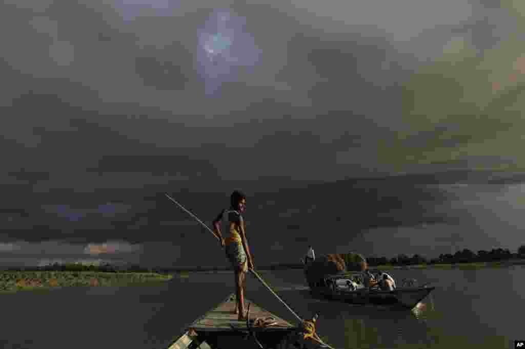 Một chiếc thuyền chở vật phẩm cứu trợ giữa lúc mây mùa mưa vần vũ chung quanh làng bị lụt Gagalmari, tại bang Assam, ngày 2 tháng 7 năm 2012