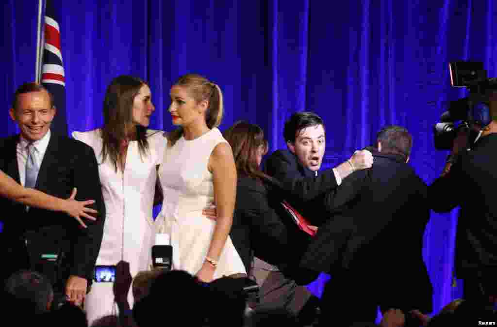 An unidentified man (3rd R) is forced off the stage by security staff after Australia's conservative leader Tony Abbott's (L) victory speech at an election night function in Sydney.