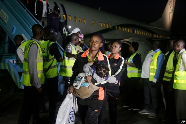 FILE - Nigerian returnees from Libya disembark from a plane upon arrival at the Murtala Muhammed International Airport in Lagos, Nigeria, Dec. 5, 2017.