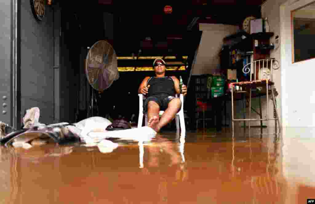 January 13: A man drinks beer as he sits in the entrance to a flooded car repair workshop in Brisbane. Flood water in Australia's third-biggest city peaked below feared catastrophic levels on Thursday but Brisbane and other devastated regions faced years