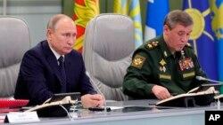 El presidente ruso Vladimir Putin y el jefe de Estado Mayor de Rusia, Valery Gerasimov, supervisan el lanzamiento de prueba del misil hipersónico Avangard, en Moscú, el miércoles 26 de diciembre de 2018.
