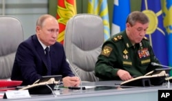 Russian President Vladimir Putin, left, and Chief of General Staff of Russia Valery Gerasimov oversee the test launch of the Avangard hypersonic glide vehicle from the Defense Ministry's control room in Moscow, Russia, Wednesday, Dec. 26, 2018