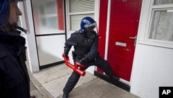 Police officers raid a property in Pimlico, London, August 12, 2011