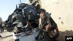 Un jihadiste armé se tient à côté de l'épave d'un avion du gouvernement syrien qui a été abattu par des militants du groupe de l'Etat islamique sur la ville syrienne de Raqa le 16 septembre 2014.