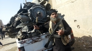 An armed jihadist stands next to the wreckage of a Syrian government forces aircraft which was shot down by militants of the Islamic State (IS) group over the Syrian town of Raqa on September 16, 2014. The plane crashed into a house in the Euphrates Valle