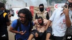 Phe Huynh đệ Hồi giáo khiêng người bị thương sau các vụ đụng độ với lực lượng an ninh chính phủ Ai Cập gần trường Ðại học Cairo, ngày 14/8/2013.