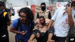 14일 이집트 기자지구에서 무르시 지지 농성을 벌이던 시위대가, 부상한 동료를 데리고 농성장을 빠져나오고 있다.