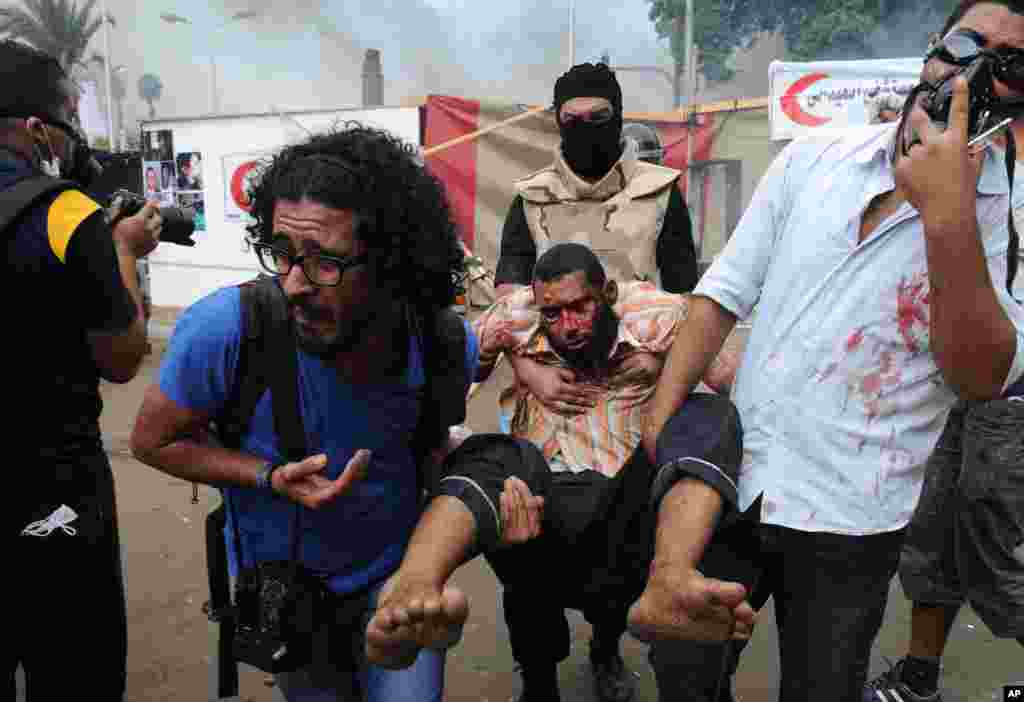Supporters of ousted Islamist President Mohammed Morsi carry another as Egyptian security forces clear a sit-in camp set up near Cairo University in Cairo's Giza district, Egypt, Wednesday, Aug. 14, 2013. Egyptian police in riot gear swept in with armored
