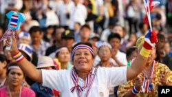 An Anti-government protester waves clapping tools at Democracy Monument in Bangkok, Thailand. (Dec. 7, 2013.)