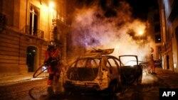 Un sapeur-pompier essaie d'éteindre le feu sur une voiture incendiée sur les Champs-Elysées après la défaite du PSG, France, le 23 août 2020.